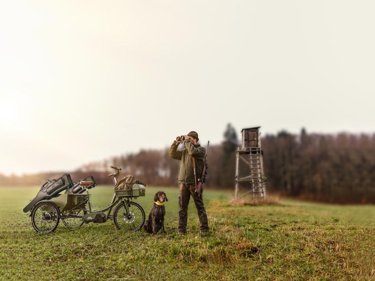 Abb. viadukt Hunter Tricycle, daneben Jäger mit Jagdhund. Im Hintergrund Wald.